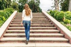 Вид сзади молодой женщины идя вверх лестницы в парке Стоковые Фотографии RF