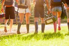 Вид сзади молодые люди идя располагаясь лагерем на музыкальном фестивале Стоковые Изображения