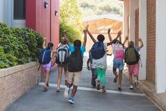 Вид сзади одноклассников бежать на кампусе школы Стоковое Изображение RF