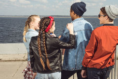 Вид сзади подростков имея потеху и представляя в парке скейтборда Стоковая Фотография