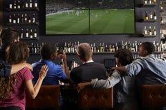 Вид сзади друзей наблюдая экран в баре совместно стоковые фотографии rf