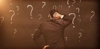 Вид сзади сомнительного бизнесмена смотря различные вопросительные знаки Стоковое Изображение