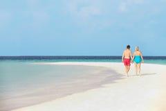 Вид сзади старших романтичных пар идя в тропическое море стоковая фотография rf