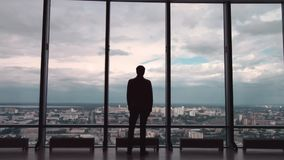 Вид сзади человека в официально сюитах которые стоят перед панорамным окном с видом на город человек стоит перед большим сток-видео