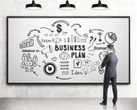 Вид сзади человека изучая бизнес-план Стоковые Изображения