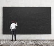 Вид сзади человека который идет написать что-то на черной доске Деревянные пол и бетонная стена Концепция умолять стоковая фотография rf