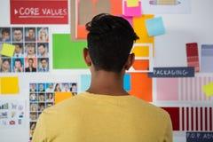 Вид сзади человека стоя против липких примечаний в офисе Стоковые Фотографии RF