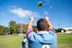 Вид сзади шарика игрока бросая пока играющ рэгби на поле Стоковые Изображения RF
