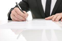 Вид спереди бизнесмена подписывая подряд Стоковое Изображение