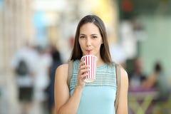 Вид спереди девушки sipping на вынос питье Стоковые Изображения RF