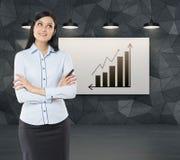 Вид спереди заботливой женщины с пересеченными руками Увеличивая диаграмма в виде вертикальных полос и стрелка на whiteboard Стоковое Фото