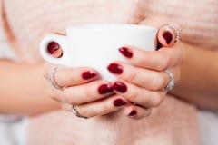 Вид спереди крупного плана женских рук держа чашку Стоковые Фото