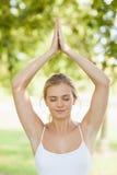 Вид спереди мирной молодой женщины делая йогу в парке Стоковые Изображения