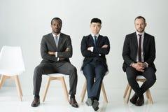 Вид спереди многонациональных бизнесменов сидя на стульях изолированных на белизне Стоковые Фото