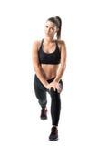 Вид спереди молодой sporty женщины протягивая ноги делая передний выпад работает Стоковое Изображение