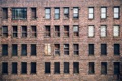 Вид спереди окон, который взошли на борт-вверх покинутых здания небоскреба кирпича от улицы в Нью-Йорке Стоковое Фото