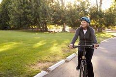 Вид спереди старшей женщины задействуя через парк Стоковые Изображения RF