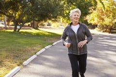 Вид спереди старшей женщины Jogging через парк Стоковая Фотография RF