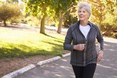 Вид спереди старшей женщины Jogging через парк Стоковое Изображение