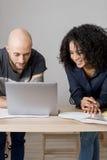 Вид спереди человека и женщины смотря компьтер-книжку Стоковые Фотографии RF
