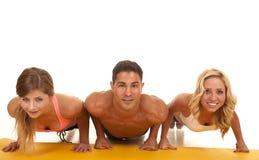 Вид спереди человека и 2 женщин нажимает поднимает стоковая фотография