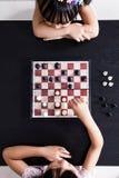 Вид с воздуха азиатских китайских маленьких сестер играя togeth шахмат Стоковые Изображения RF