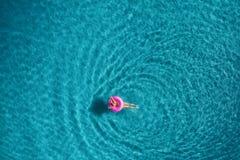 Вид с воздуха заплывания молодой женщины на розовом кольце заплыва Стоковые Фотографии RF