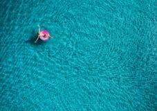 Вид с воздуха заплывания молодой женщины на розовом кольце заплыва Стоковые Фото