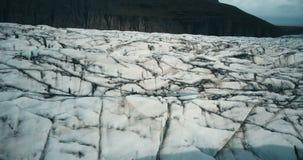 Вид с воздуха конца-вверх ледника Vatnajokull с черной золой Трутень летая над большим айсбергом в Исландии видеоматериал