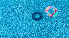 Вид с воздуха красочной раздувной игрушки донута кольца в бассейне мочит сверху Стоковые Изображения