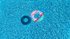 Вид с воздуха красочной раздувной игрушки донута кольца в бассейне мочит сверху Стоковое Фото