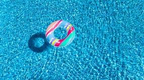 Вид с воздуха красочной раздувной игрушки донута кольца в воде бассейна сверху, концепция семейного отдыха Стоковые Фото