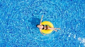 Вид с воздуха молодого заплывания женщины брюнет на раздувном большом желтом цвете в бассейне Взгляд сверху тонкой дамы ослабляя  Стоковые Фотографии RF