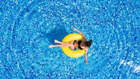 Вид с воздуха молодого заплывания женщины брюнет на раздувном большом желтом цвете в бассейне Взгляд сверху тонкой дамы ослабляя  Стоковое Фото