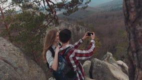 Вид с воздуха молодых прелестных людей принимая selfie на верхней части горы, усмехаться, и смеяться над Шикарный пейзаж видеоматериал