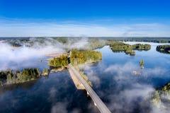 Вид с воздуха дороги между озерами в тумане утра Стоковое Изображение
