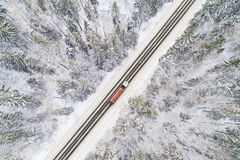 Вид с воздуха дороги с красной тележкой в лесе зимы стоковые изображения