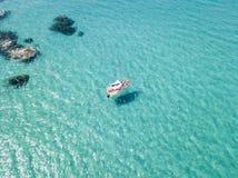 Вид с воздуха причаленной шлюпки плавая на прозрачное море Стоковые Фото
