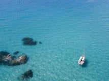 Вид с воздуха причаленной шлюпки плавая на прозрачное море Стоковое Изображение
