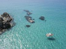 Вид с воздуха причаленной шлюпки плавая на прозрачное море Стоковые Изображения