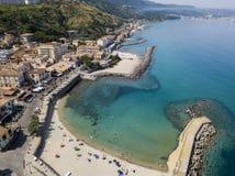 Вид с воздуха пляжа с каное, шлюпками и зонтиками Пристань Pizzo Calabro, панорамного взгляда сверху Стоковые Изображения