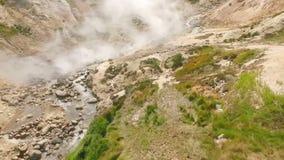 вид с воздуха Сильные потоки термальной весны из земли Вода горячего источника в горах видеоматериал