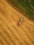 Вид с воздуха трактора делая связку сена свертывает в поле Стоковые Фотографии RF