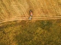 Вид с воздуха трактора делая связку сена свертывает в поле Стоковое Фото