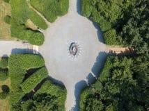 Вид с воздуха фонтана и цвести садовничают с flowerbeds и вазами Стоковая Фотография