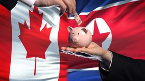Вклад Канады в руке Северной Кореи кладя деньги в предпосылку флага piggybank акции видеоматериалы