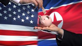 Вклад США в Северной Корее, руке кладя деньги в piggybank на предпосылку флага акции видеоматериалы