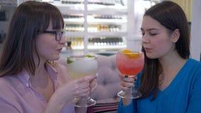 Вкусная диета, красивые счастливые девушки связывает и выпивая сок через солому от больших стекел в ресторане акции видеоматериалы