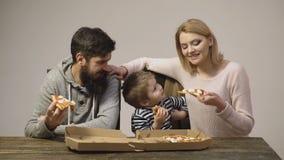 Вкусная пицца Мальчик с родителями имея кусок пиццы Голодный ребенок принимая укус от пиццы Концепция питания видеоматериал
