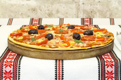 Вкусная пицца с овощами, базилик, оливки, томаты, зеленый перец на разделочной доске, красочном ткани таблицы традиционное Стоковые Изображения